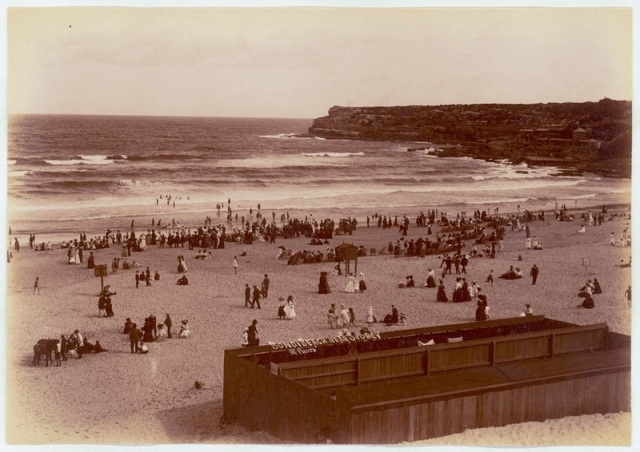 Bondi Beach c.1905-1909. The men's surf sheds were the subject of extensive criticism. Deemed filthy and inadequate, men changing inside could be easily seen from the nearby tram waiting shed. (State Library of NSW)