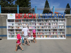 A family wanders past the books on offer in the Coogee Beach Library